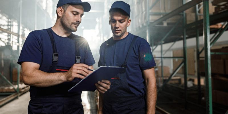 funcionários em um estoque de fábrica revisando procedimentos de operação com prancheta