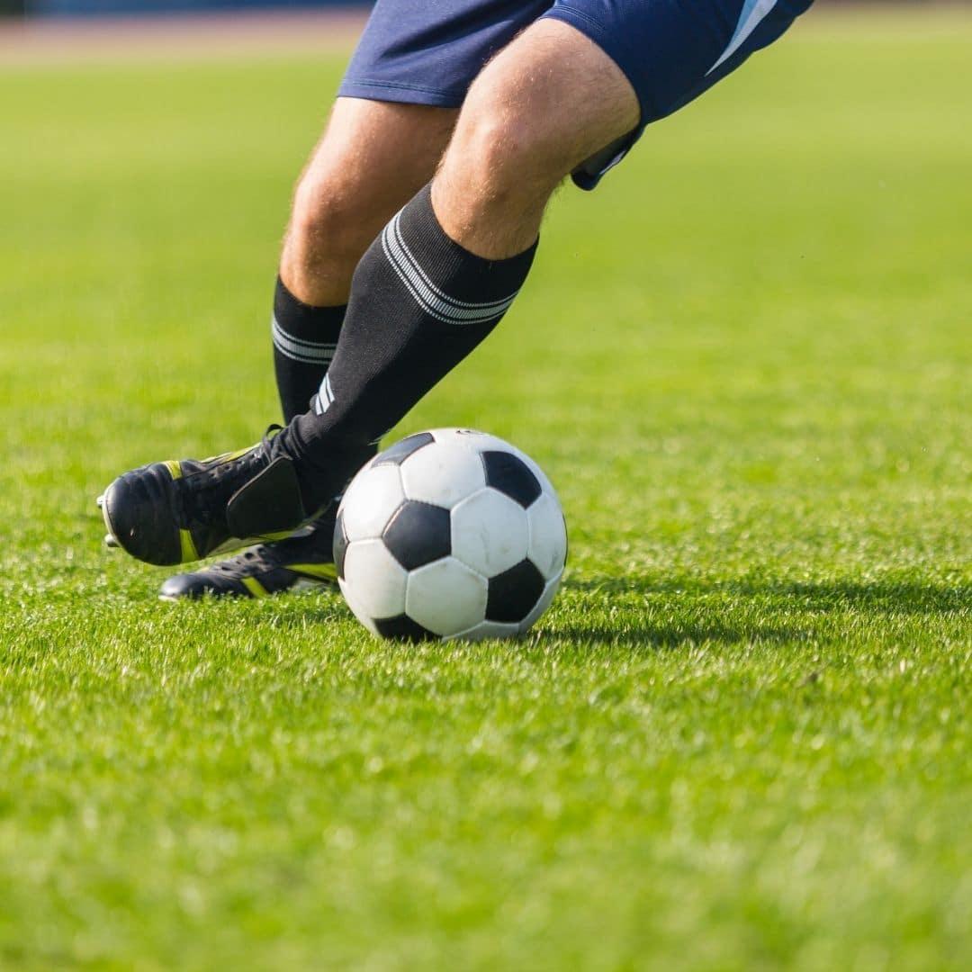 jogador de futebol driblando em um gramado verde