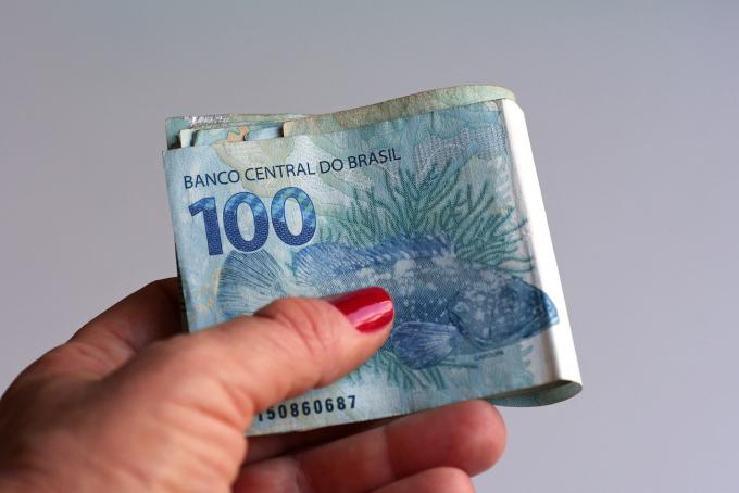 Mão feminina segurando dinheiro brasileiro (real / arroz)