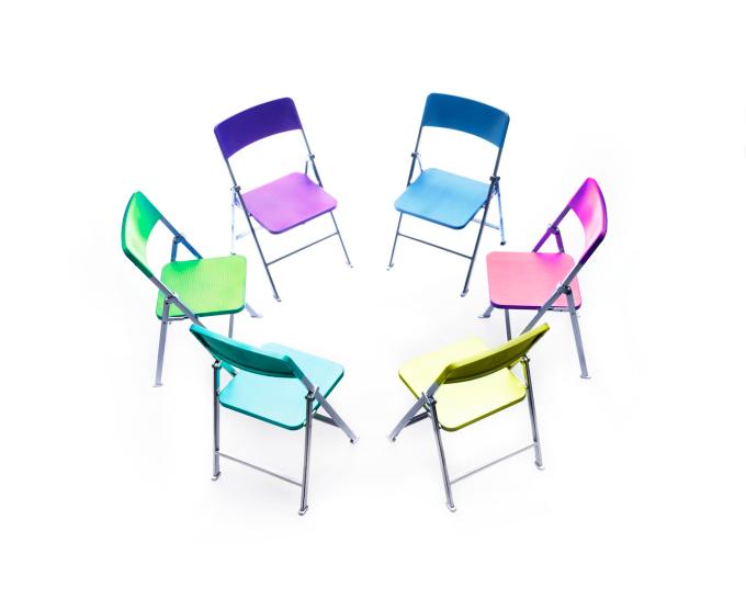 Círculo de cadeiras de cores diferentes.